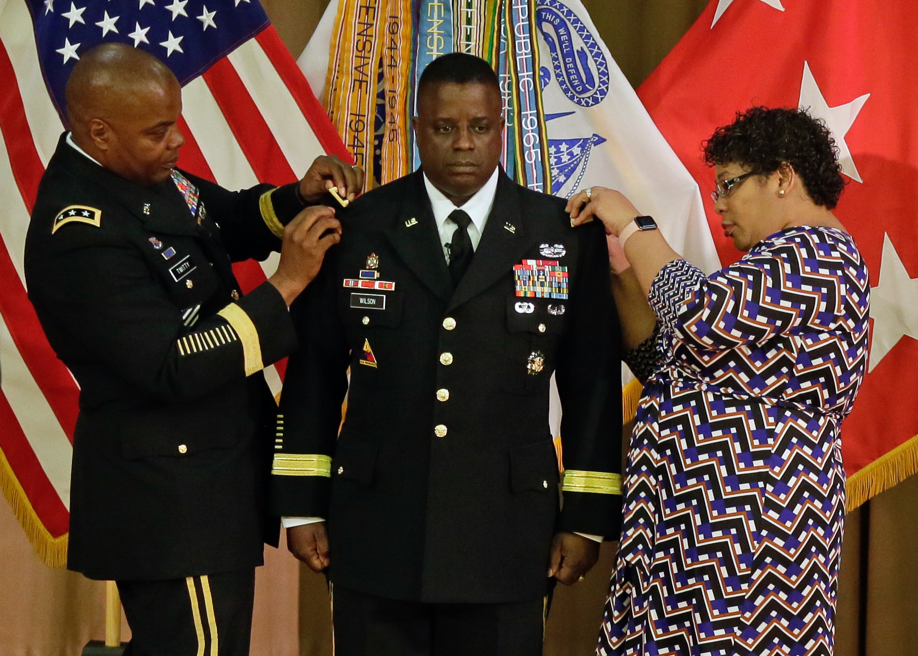 Brig. Gen. David Wilson, Chief of Ordnance, stands at attention while Lt. Gen. Stephen Twitty, commanding general, First Army, and Patricia Wilson, his spouse, place brigadier general epaulets on his jack during his promotion ceremony April 13 at the Citadel.